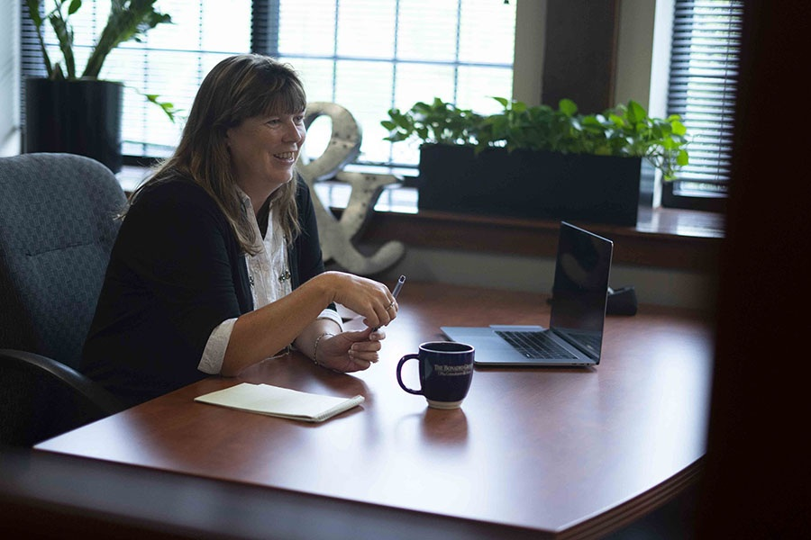 Paula Deckman speaking at her desk with a computer and coffee mug